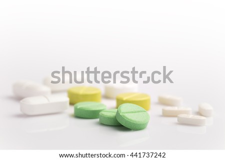 Medicine pills in various shapes, colors, and sizes on white background with selective focus on the front green pill, room for copyspace on the top - stock photo