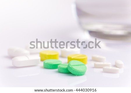 Medicine pills in various shapes, colors, and sizes on white background with selective focus on the front green pill with blur glass of water in the background, room for copyspace on the top - stock photo