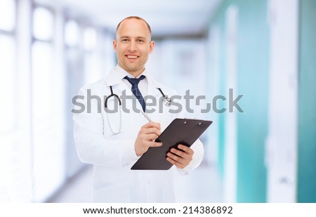 medicine, profession and healthcare concept - smiling male doctor with clipboard and stethoscope writing prescription over hospital background