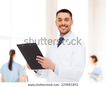 medicine, profession, and healthcare concept - smiling male doctor with clipboard writing prescription over white background - stock photo