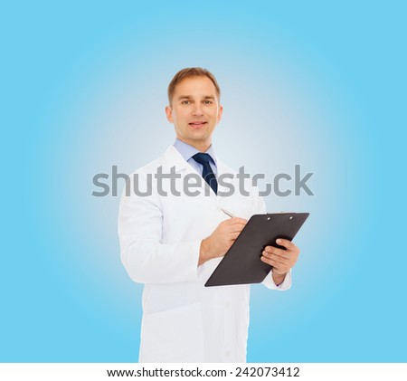 medicine, profession and healthcare concept - smiling male doctor with clipboard writing prescription over blue background - stock photo