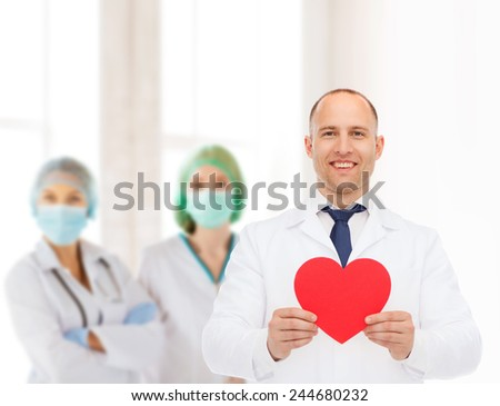 medicine, profession, charity and healthcare concept - smiling male doctor with red heart over group of medics - stock photo