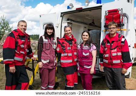 medicine, profession, teamwork and health care concept - group of smiling paramedics on ambulance background