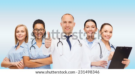 medicine, profession, teamwork and healthcare concept - international group of smiling medics or doctors with clipboard and stethoscopes with showing thumbs up over blue background - stock photo