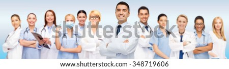 medicine, profession, teamwork and healthcare concept - international group of smiling medics or doctors with clipboard and stethoscopes over blue background