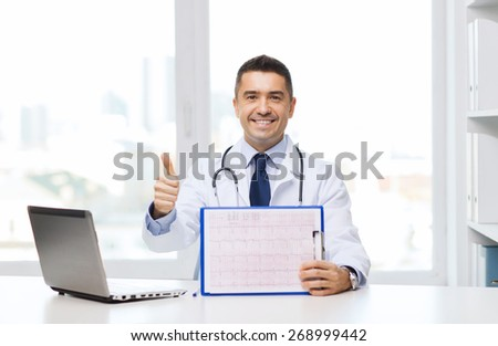 medicine, profession, technology and people concept - happy male doctor with clipboard and laptop computer showing thumbs up in medical office - stock photo