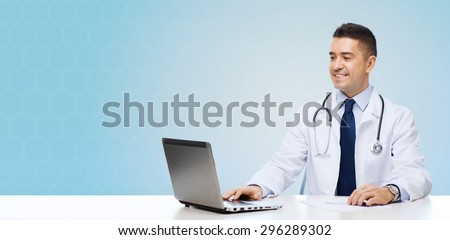 medicine, profession, technology and people concept - smiling male doctor sitting at table with laptop and stethoscope over blue background - stock photo