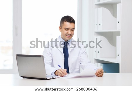 medicine, profession, technology and people concept - smiling male doctor with laptop in medical office - stock photo
