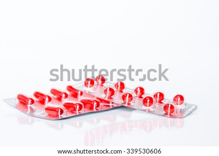 Medicine red pills or capsules on white background with copy space. Drug prescription for treatment medication. Pharmaceutical medicament, cure in container for health. Antibiotic closeup