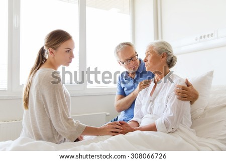 medicine, support, family health care and people concept - senior man and young woman visiting and cheering her ill grandmother at hospital ward - stock photo