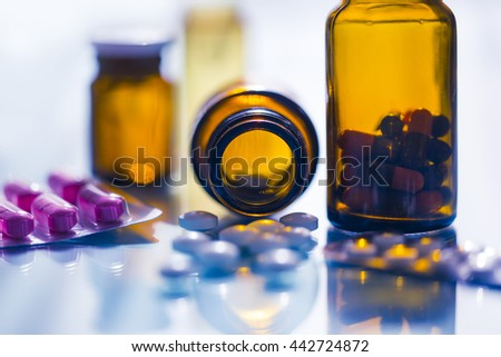medicines in blister packaging and brown glasses in backlight - stock photo