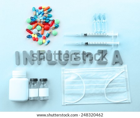 Medicines with word Influenza on light background - stock photo