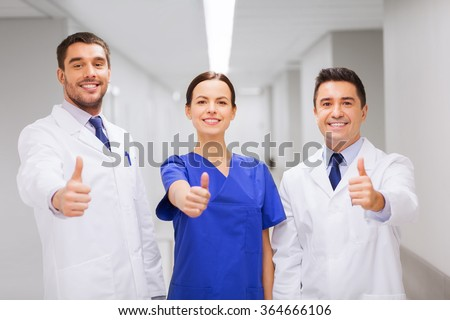 medics or doctors at hospital showing thumbs up - stock photo