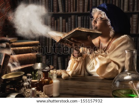 Medieval alchemist blowing dust off the old books in her laboratory - stock photo