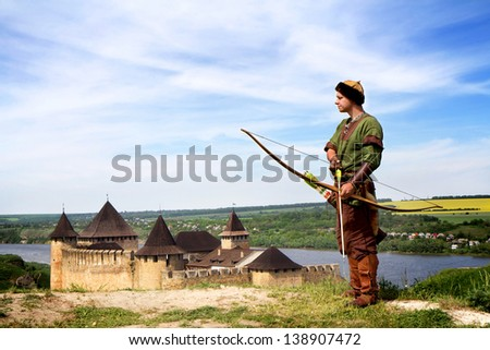 Medieval archer with bow and arrows on castle background - stock photo