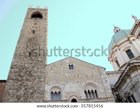 Medieval architecture facade.The oldest public building in the city.  Baroque church in the background. Brescia, Italy.  - stock photo
