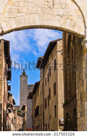 Medieval architecture of San Gimignano, towers and houses in narrow street, Tuscany, Italy