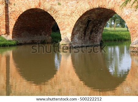 medieval bridge made of red brick with two arches over the river in Europe