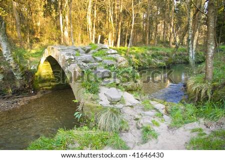medieval bridge over a stream.twelfth century bridge - stock photo