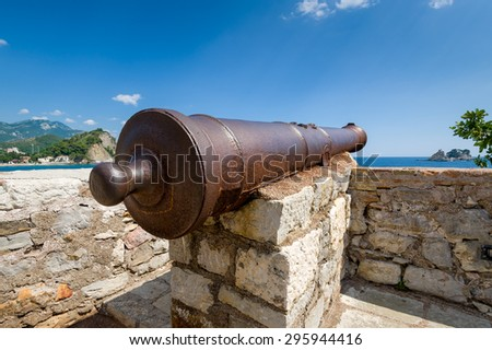 Medieval cannon gun fish-eye look. Petrovac old town fortress. Montenegro - stock photo