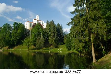 Medieval castle over lake scene - stock photo