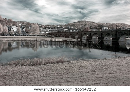 Medieval city of Ponte de Lima with his old bridge, north of Portugal. Used infrared filter. - stock photo