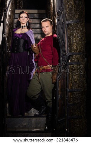 Medieval couple on the stairs in castle - stock photo