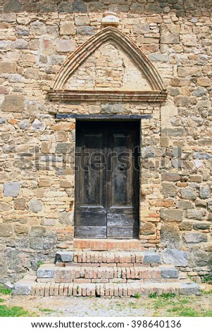 Medieval doorway in a stone wall in the fortress at Montalcino, Italy