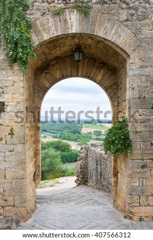 Medieval Doorway Leading to Tuscany - Arched doorway in a medieval stone wall in the Tuscan village of Monteriggioni, Italy.  Concepts could include travel, architecture, European heritage, others. - stock photo