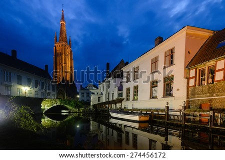 Medieval european city in lights by night reflected in the water of canals. Brugge, Belgium. - stock photo