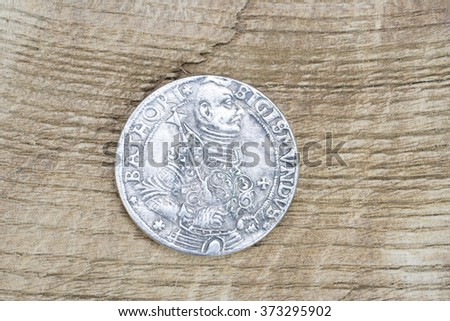 Medieval European silver coin on wooden bank