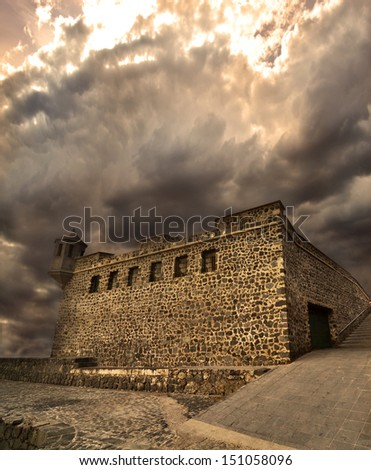 Medieval fortress under golden dramatic skies - stock photo