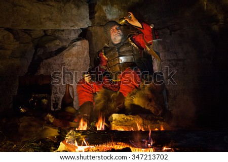 Medieval King in armor is looking at the empty cup of wine to find some drops. - stock photo