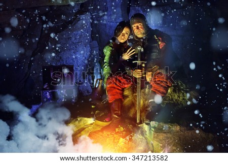 Medieval King in armor with sword is sitting on furs near the camp fire with his princess. Snow falls.