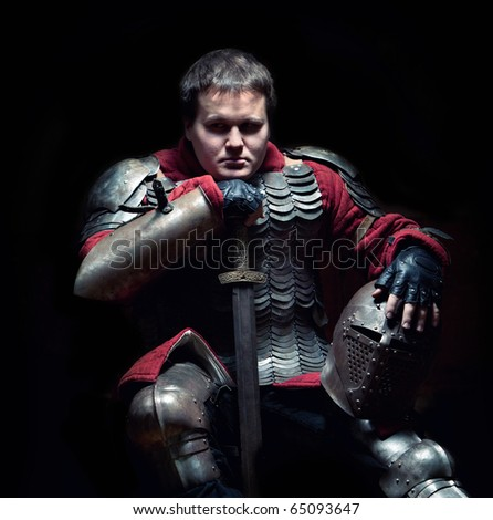Medieval knight in the armor with the sword and helmet. Portrait in the shadows.