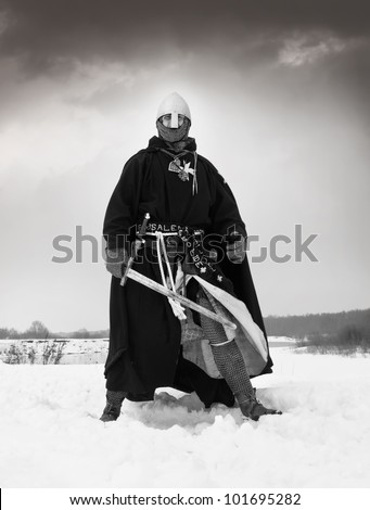 Medieval knight of St. John (Hospitallers) with a sword - stock photo