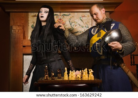 Medieval knight plays chess with death in a castle - stock photo