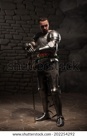 Medieval Knight posing with sword  and helmet in a dark stone background. Full-length portrait.