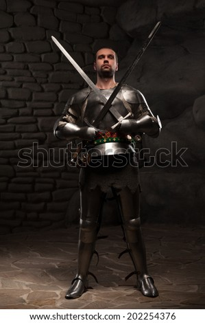 Medieval Knight posing with two swords crossed on chest on a dark stone wall background - stock photo