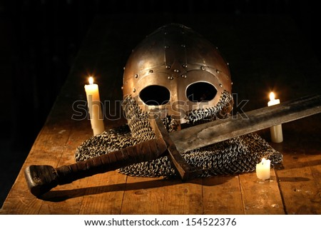 Medieval knight sword and helmet near lighting candles
