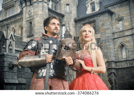 Medieval knight with his beloved lady. Ancient castle on the background. - stock photo