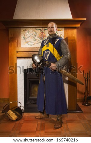 Medieval knight with sword against fireplace  - stock photo