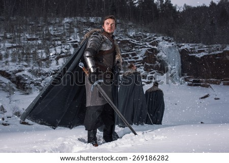 Medieval knight with sword in armor as style Game of Thrones in Winter Rock Landscapes - stock photo