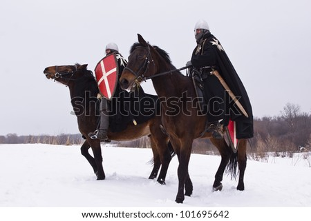 Medieval knights of St. John (Hospitallers) on a bay horses - stock photo