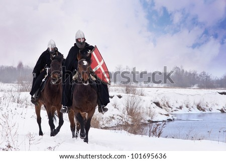 Medieval knights of St. John (Hospitallers) riding on a bay horses - stock photo