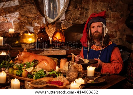 Medieval man eat and drink in ancient castle kitchen interior.