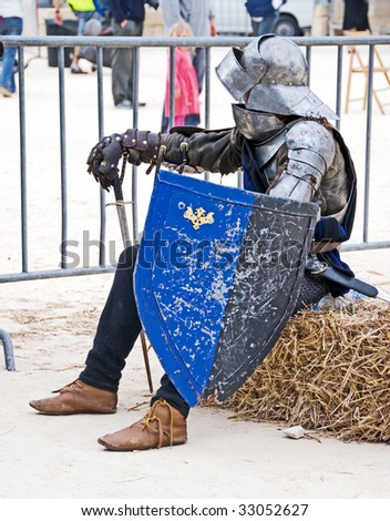 Medieval Re-enactment - knight reclining on a straw bale - stock photo