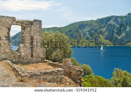 medieval ruins of byzantine church with white yacht in Aegean sea and mountains at background, Marmaris, Turkey - stock photo