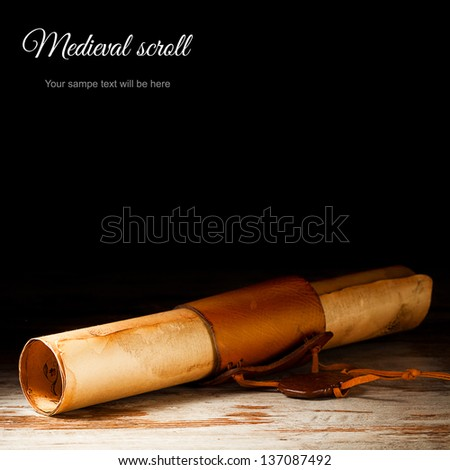 medieval scroll over grunge wooden table - stock photo