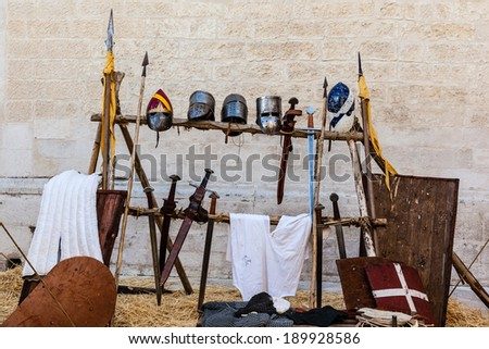 medieval shields, helm and weapons in a medieval fair in italy - stock photo
